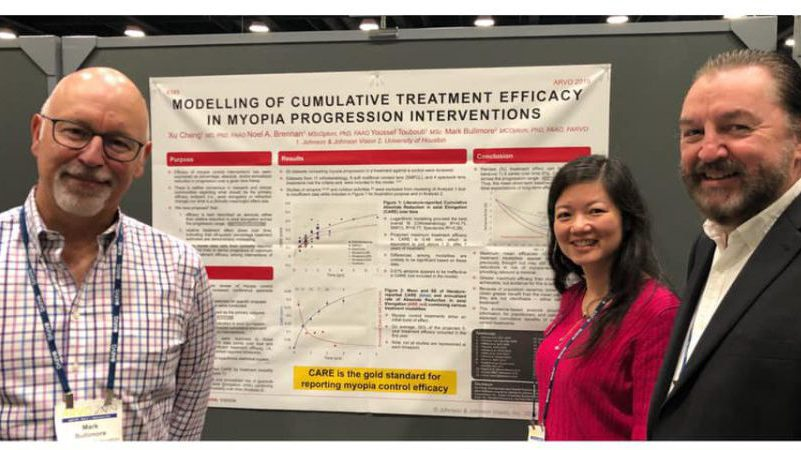 "Xu Cheng (Cathy), Noel Brennan and Mark Bullimore standing in front of their poster titled ""Modelling of Cumulative Treatment Efficacy in Myopia Progression Interventions"