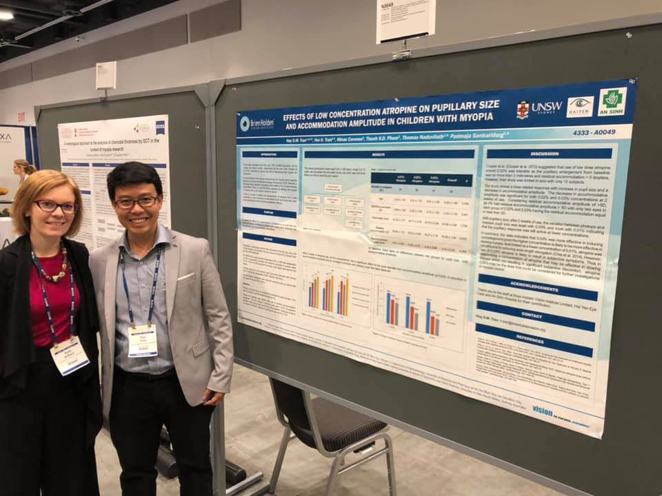 Trần Đình Minh Huy and Kate in front of his poster titled: Effects of Low Concentration Atropine on Pupillary Size and Accommodation Amplitude in Children with Myopia