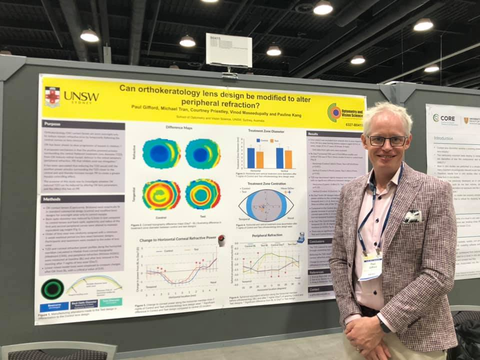 "Paul ARVO2019 in front of his poster titled ""Can orthokeratology lens design be modified to alter peripheral refraction"""